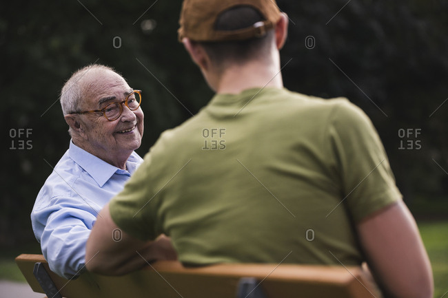 Portrait of smiling senior man relaxing together with his grandson on a park bench