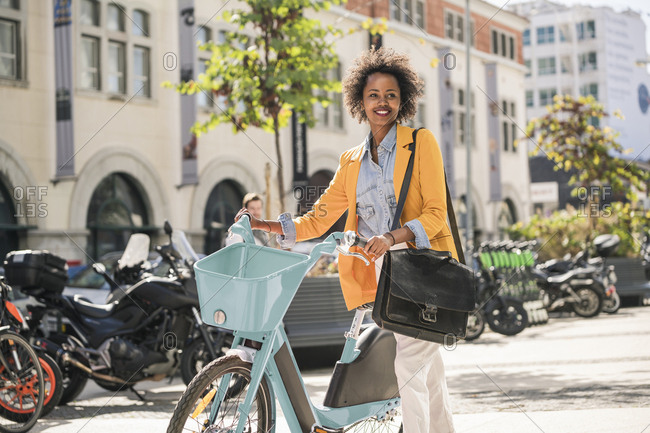 Smiling young woman with bicycle in the city on the go