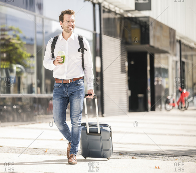 Smiling young man with rolling suitcase in the city on the go