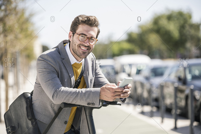 Portrait of smiling young businessman with cell phone and e-scooter in the city