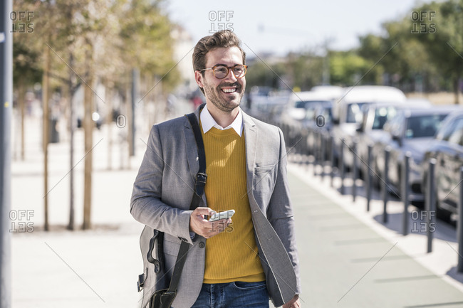 Smiling young businessman with cell phone in the city on the go