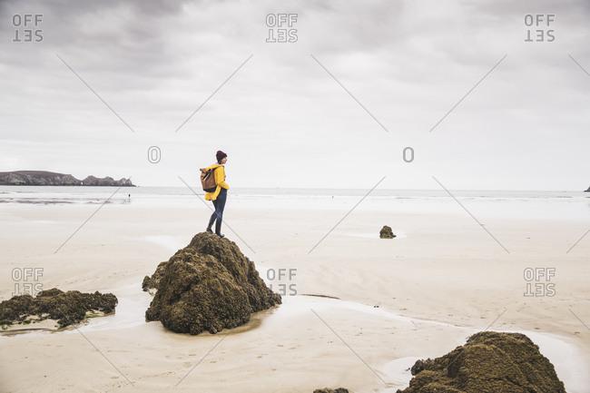 Young woman wearing yellow rain jacket at the beach- Bretagne- France