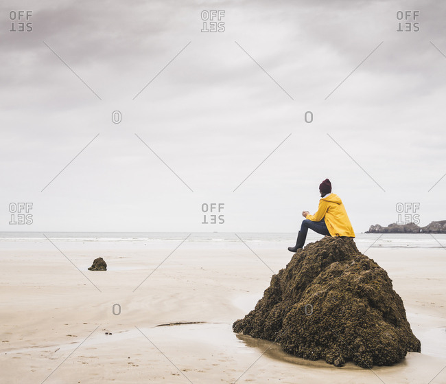 Young woman wearing yellow rain jacket sitting on rock at the beach- Bretagne- France