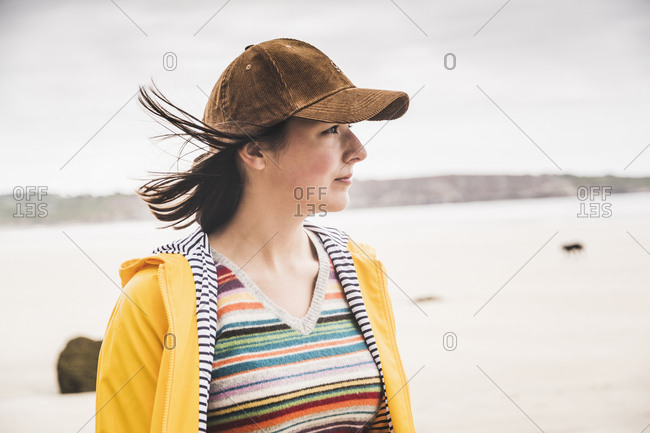 Portrait of young woman wearing yellow rain jacket at the beach- Bretagne- France