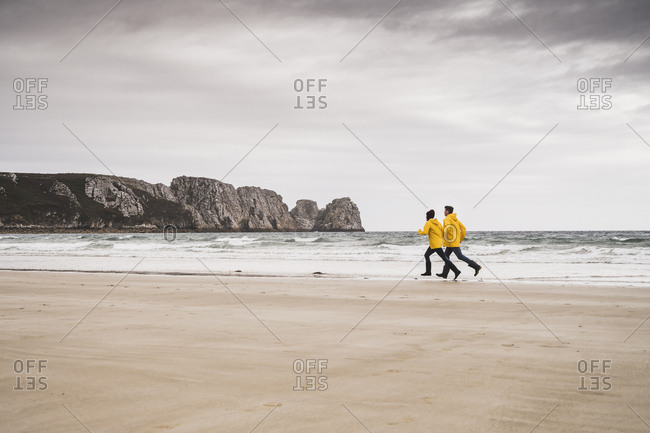 Young woman wearing yellow rain jackets and running at the beach- Bretagne- France