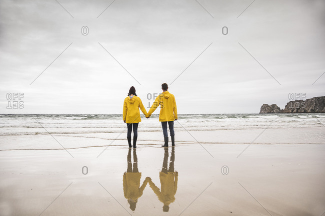 Young woman wearing yellow rain jackets and standing at the beach- Bretagne- France