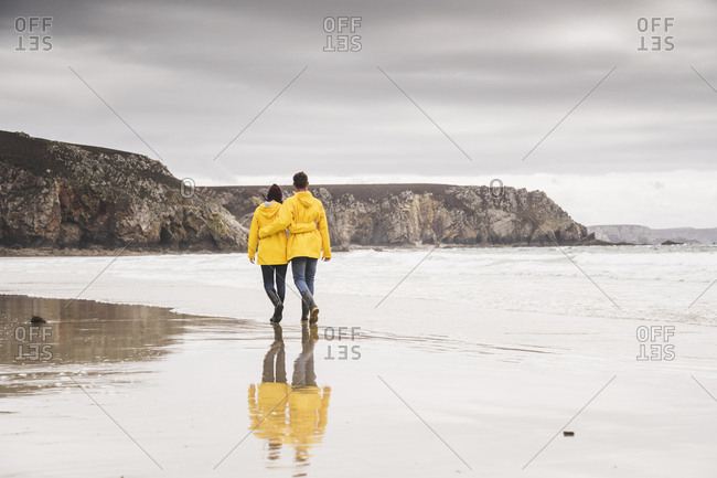 Young woman wearing yellow rain jackets and walking along the beach- Bretagne- France