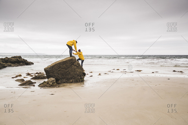Young woman wearing yellow rain jackets and climbing on a rock at the beach- Bretagne- France