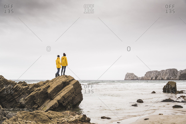 Young woman wearing yellow rain jackets and standing on rock at the beach- Bretagne- France