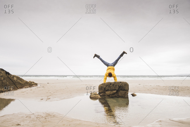Young man wearing yellow rain jacket at the beach and doing a handstand on rock- Bretagne- France