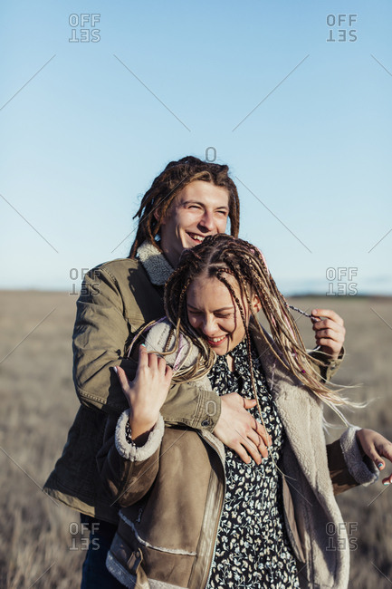 Happy couple with dread locks embracing in a field, Lleida, Spain