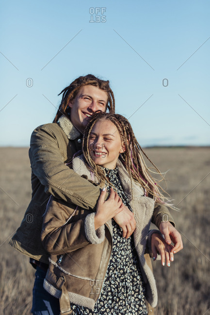 Young couple with dread locks embracing in a field, Lleida, Spain