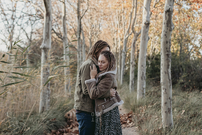 Couple with dread locks embracing in nature, Lleida, Spain