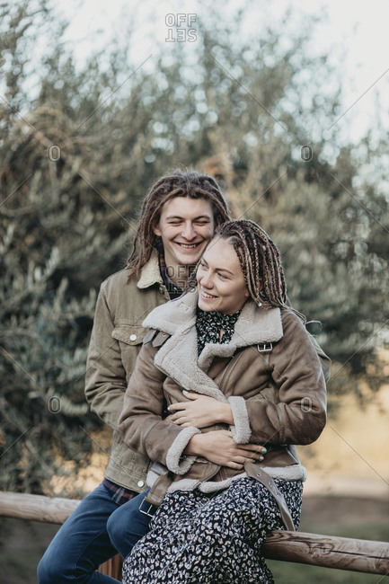 Man with dread locks giving girlfriend a piggyback ride in the woods, Lleida, Spain