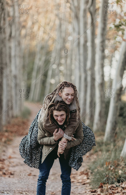 Couple with dread locks embracing in a field, Lleida, Spain