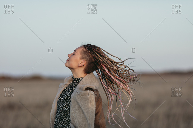 Portrait of a young woman with her dreadlocks blowing in the wind