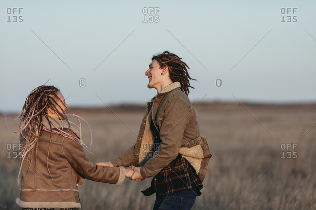 Couple with dread locks dancing in a field, Lleida, Spain