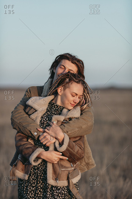 Couple with dread locks embraced in a field, Lleida, Spain