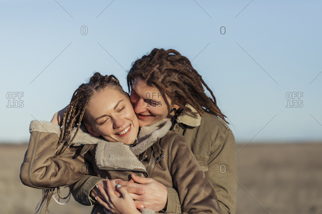 Young lovers with dread locks embracing in a field, Lleida, Spain
