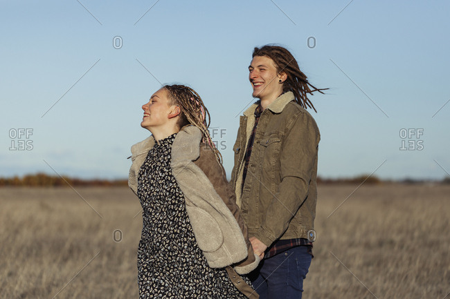 Young lovers with dread locks holding hands while walking in a field, Lleida, Spain