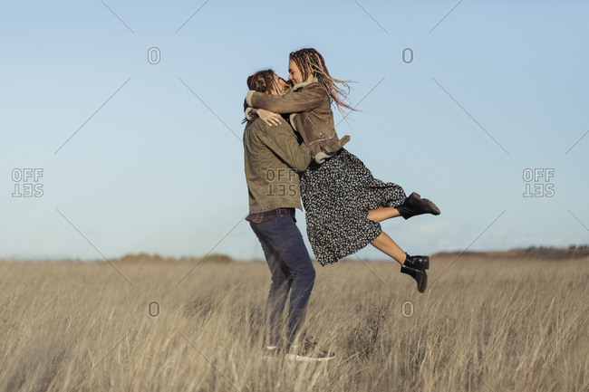 Young couple with dread locks dancing in a field, Lleida, Spain