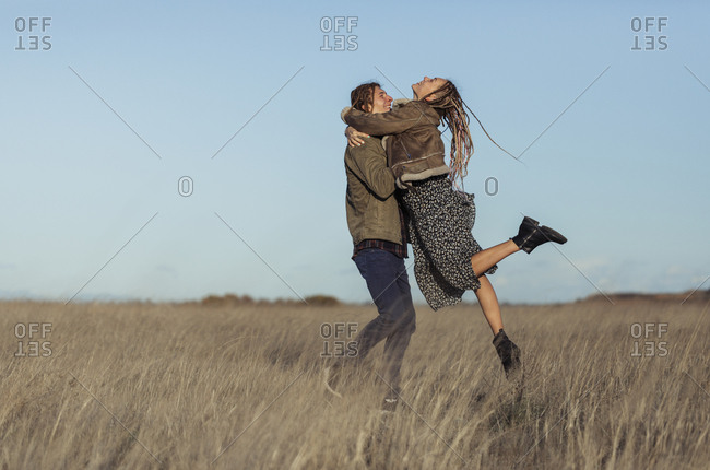 Couple with dread locks dancing in a field
