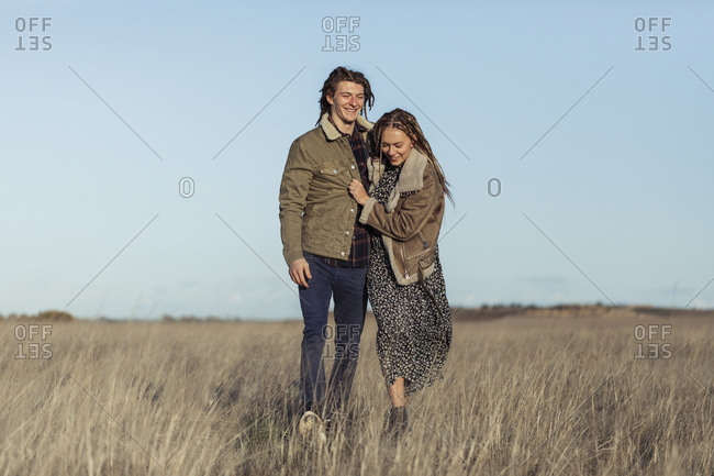 Young couple with dread locks walking together in a field, Lleida, Spain