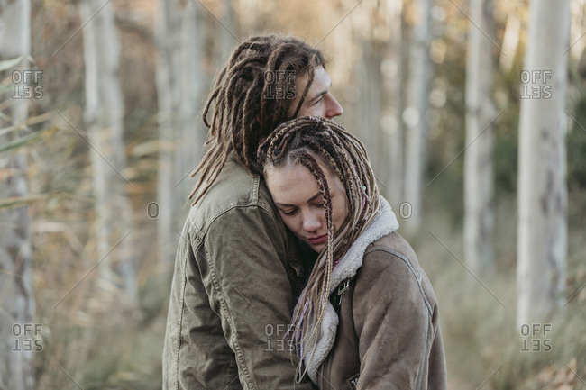 Young couple with dread locks standing together in the woods, Lleida, Spain