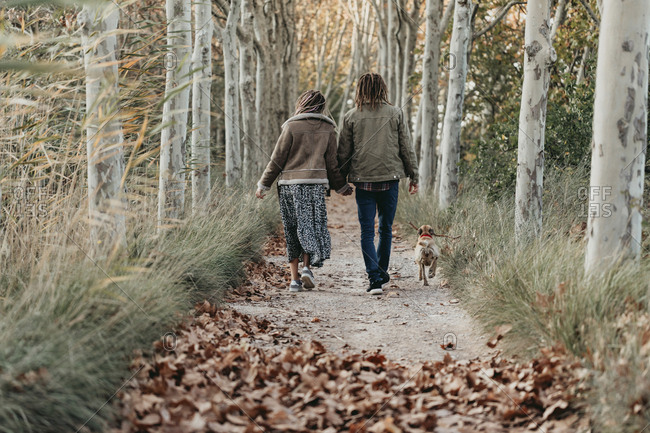 Couple with dread locks walking with dog on a path in the woods, Lleida, Spain