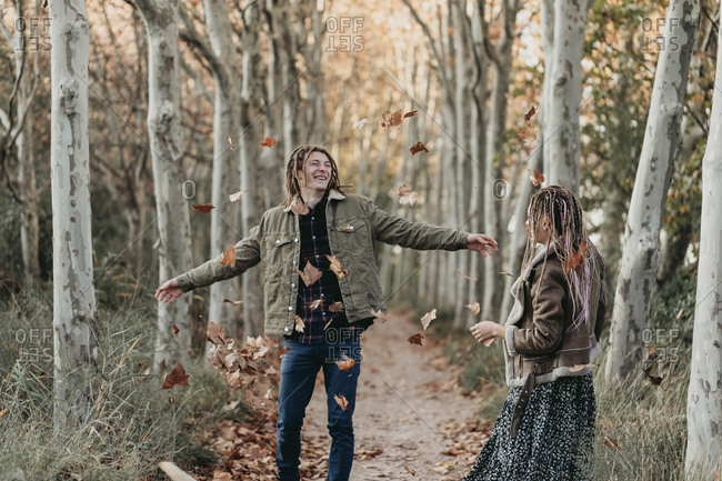 Young couple with dread tossing leaves in the air on a path in the woods