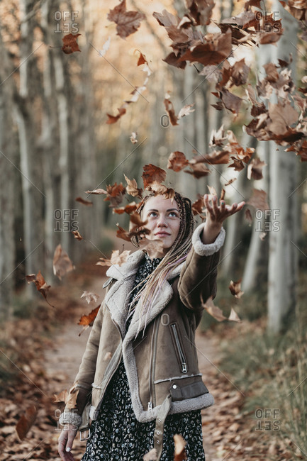 Young woman with dread tossing leaves in the air on a path in the woods