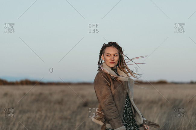 Portrait of a young woman with dreadlocks standing in a field at sunset