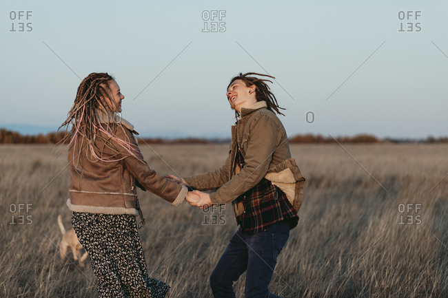 Couple with dread locks having fun and dancing in a field, Lleida, Spain