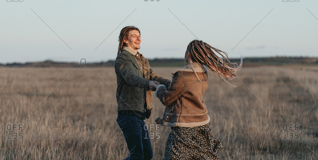 Young couple with dread locks having fun and dancing in a field, Lleida, Spain