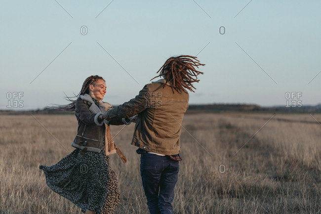 Couple with dread locks having fun and dancing in a field