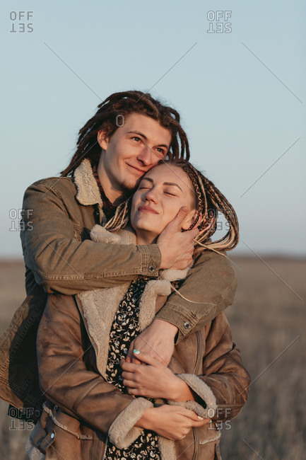 A young couple with dread locks embracing in a field at sunset