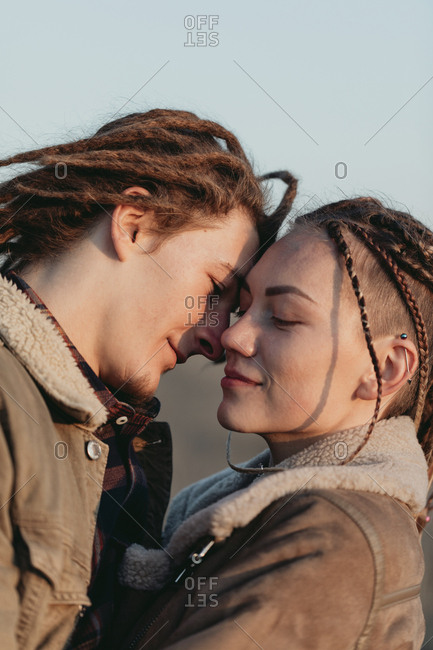 Couple with dread locks standing close in a field, Lleida, Spain
