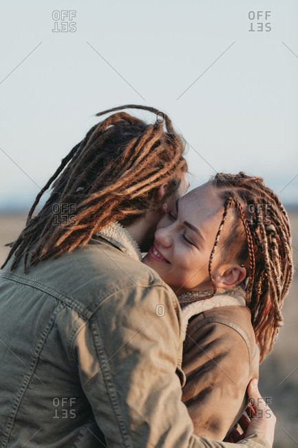 Happy young couple with dread locks embracing in a field