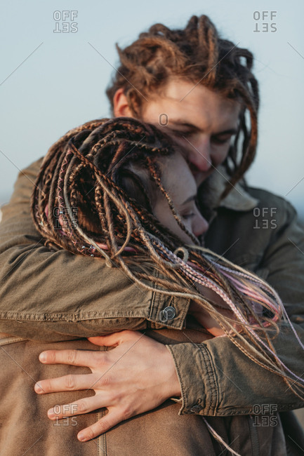 Young man with dread locks embracing his girlfriend in a field, Lleida, Spain