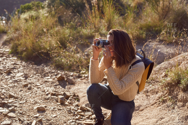 Young woman crouching on a rocky mountain path holding a camera and taking a photo