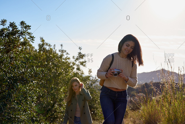 Two attractive young women walking outdoors and taking photos