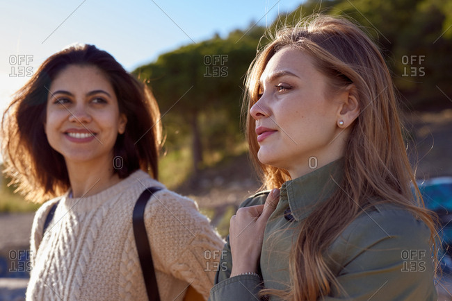 Two young women standing together on a mountain path as they look into the distance