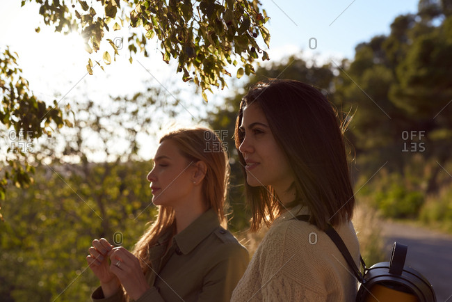 Two young woman standing outdoors near a green leafy tree looking away