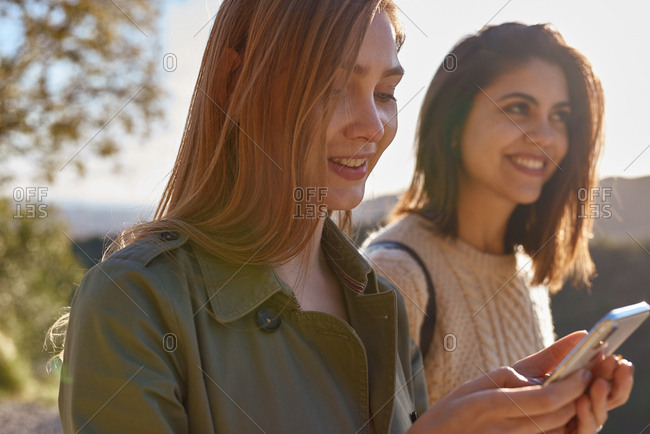 Young woman looking down a cell phone while her friend smiles and looks up