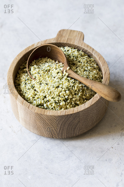 Shelled hemp seeds in a wooden bowl with spoon