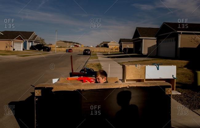 Boy hiding behind furniture on sidewalk with toy gun
