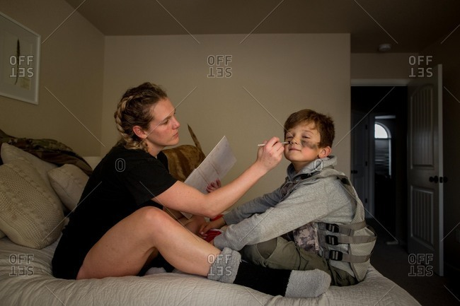 Woman sitting on bed painting little boy's face in camouflage