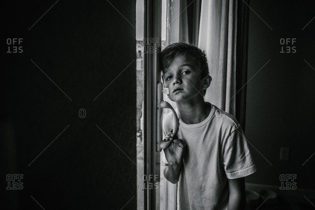 Boy leaning on sliding door with bored expression in black and white