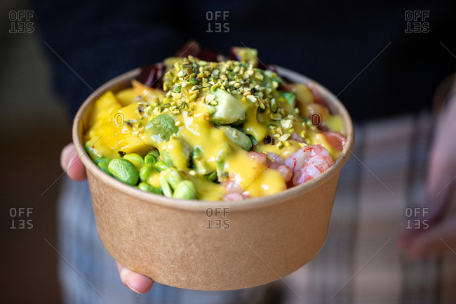 Woman holding dish filled with veggies and shrimp