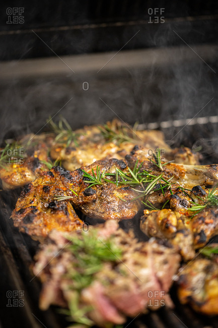Meat on a grill with rosemary